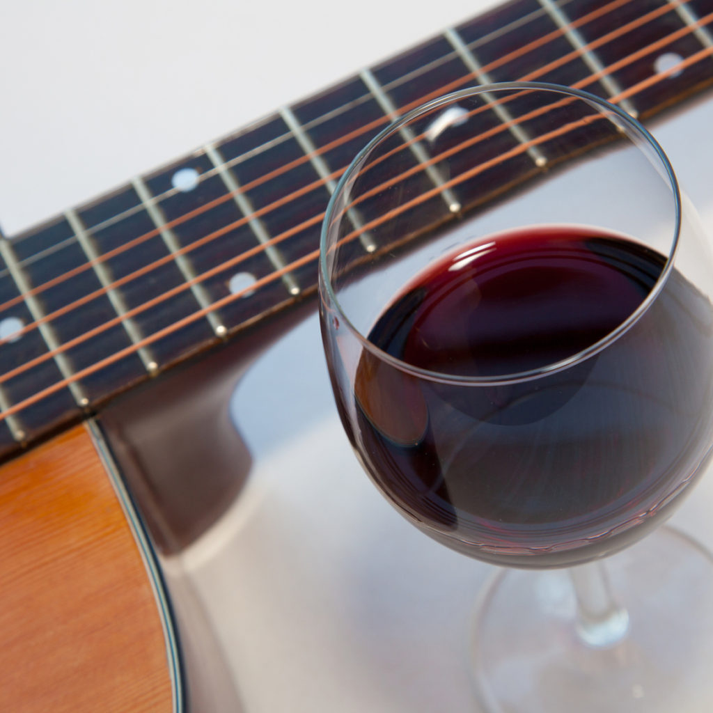 Glass of red wine and a part of acoustic guitar. White background with shadows.